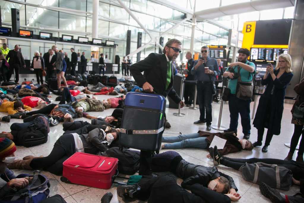 Protesters against a possible third runway at Heathrow and aviation in general for contributing to climate change stage a flash mob die-in and theatrical 'Frequent-fliers-high-polluters club theater' at terminal 2 at Heathrow, London, Oct 1st 2016.